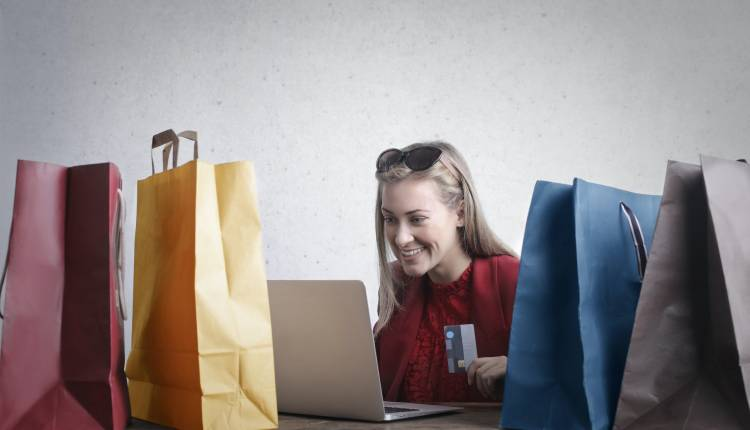 blonde female customer looking at a laptop surrounded by shopping bags and holding a credit card