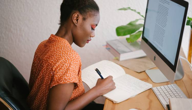 black woman creating relevant content in notebook